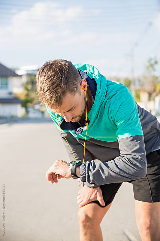 A fit young male runner checking his watch  by Jovo Jovanovic for Stocksy United