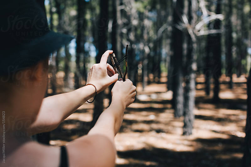 Girl in the forest playing with a little homemade slingshot by Jacqui Miller for Stocksy United