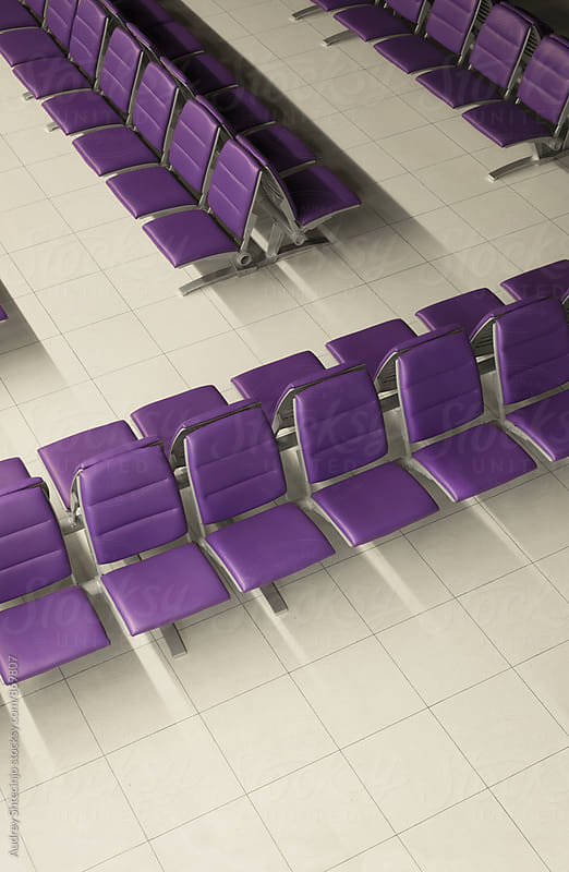 Purple chairs in airport waiting space by Audrey Shtecinjo for Stocksy United
