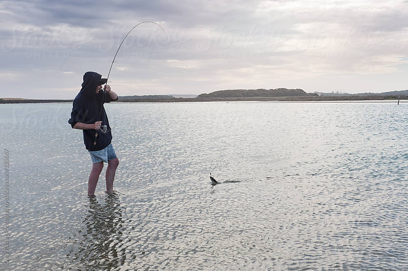 Wading Angler in last stage of landing a Southern Black Bream by Gary Radler Photography for Stocksy United