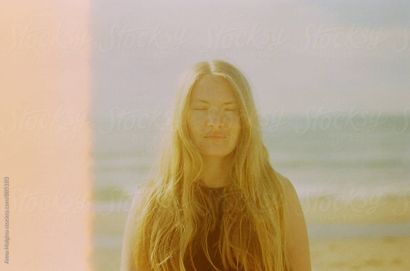 A film portrait of young beautiful blond woman with closed eyes made with expired film by Anna Malgina for Stocksy United