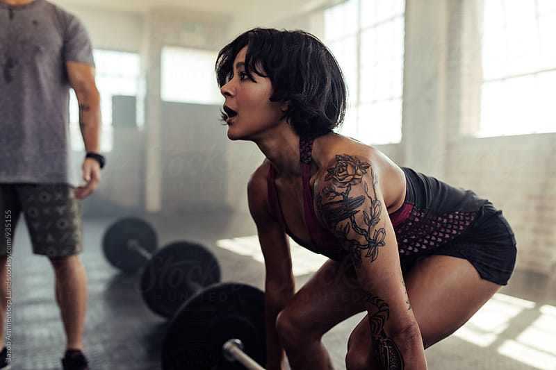 Determined young woman training with barbell at gym by Jacob Lund for Stocksy United