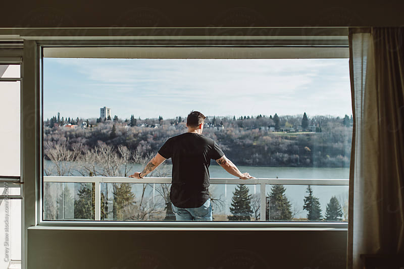 Portrait of urban male and cityscape through picture window by Carey Shaw for Stocksy United
