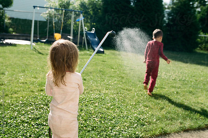 little girl sprays hose at brother by Maria Manco for Stocksy United