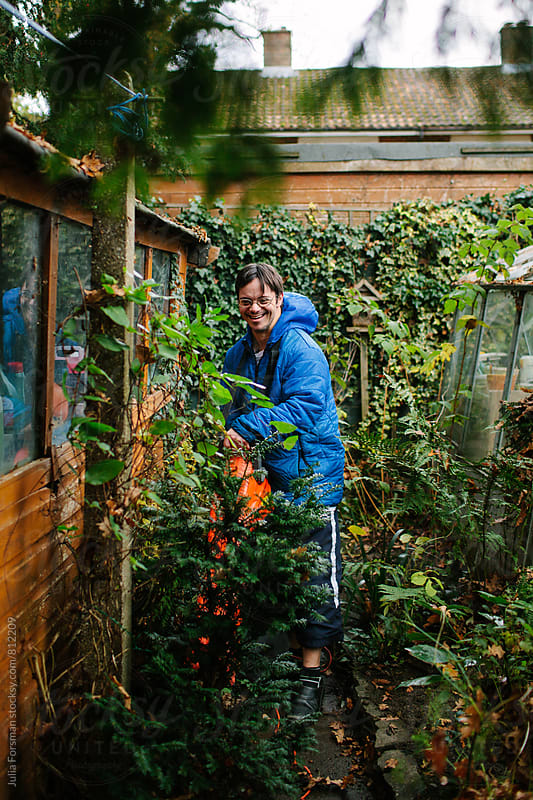 Man with learning disabilities using a leaf blower in a garden. by Julia Forsman for Stocksy United