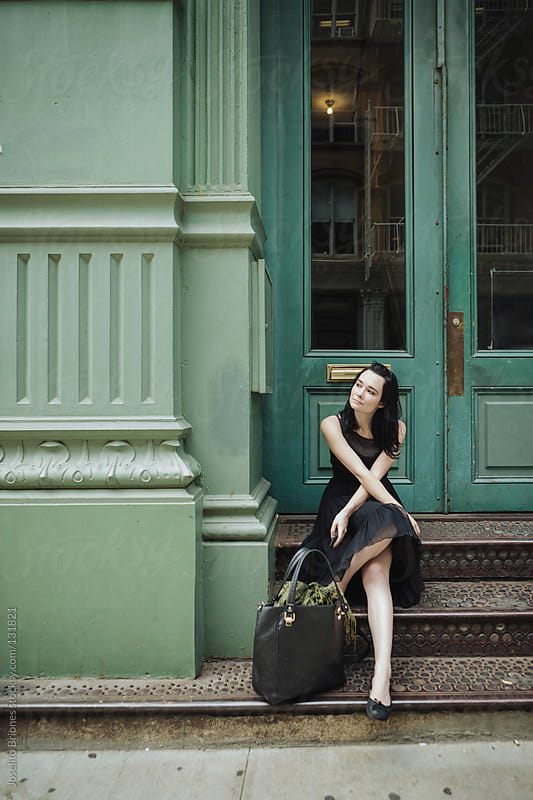 Portrait of a Woman Sitting Outside a Shop in Soho, New York by Joselito Briones for Stocksy United