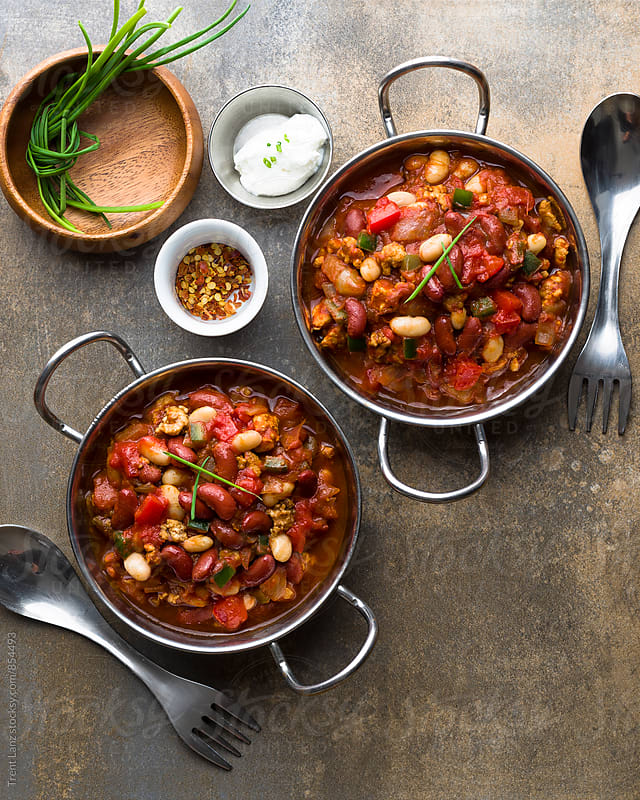 Delicious turkey chili in two saucepans by Trent Lanz for Stocksy United