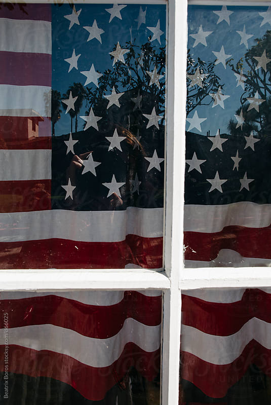 United States flag behind a closed window  by Beatrix Boros for Stocksy United