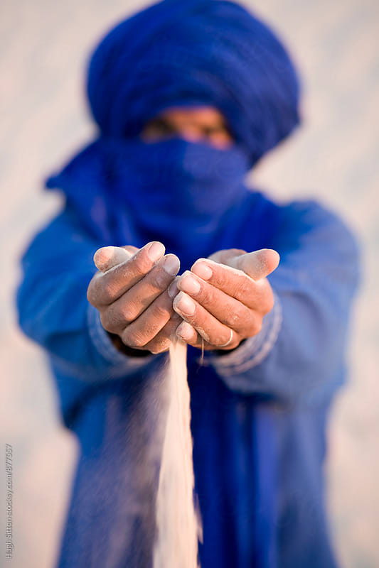Berber sifting sand through his hands. Sahara Desert.  by Hugh Sitton for Stocksy United