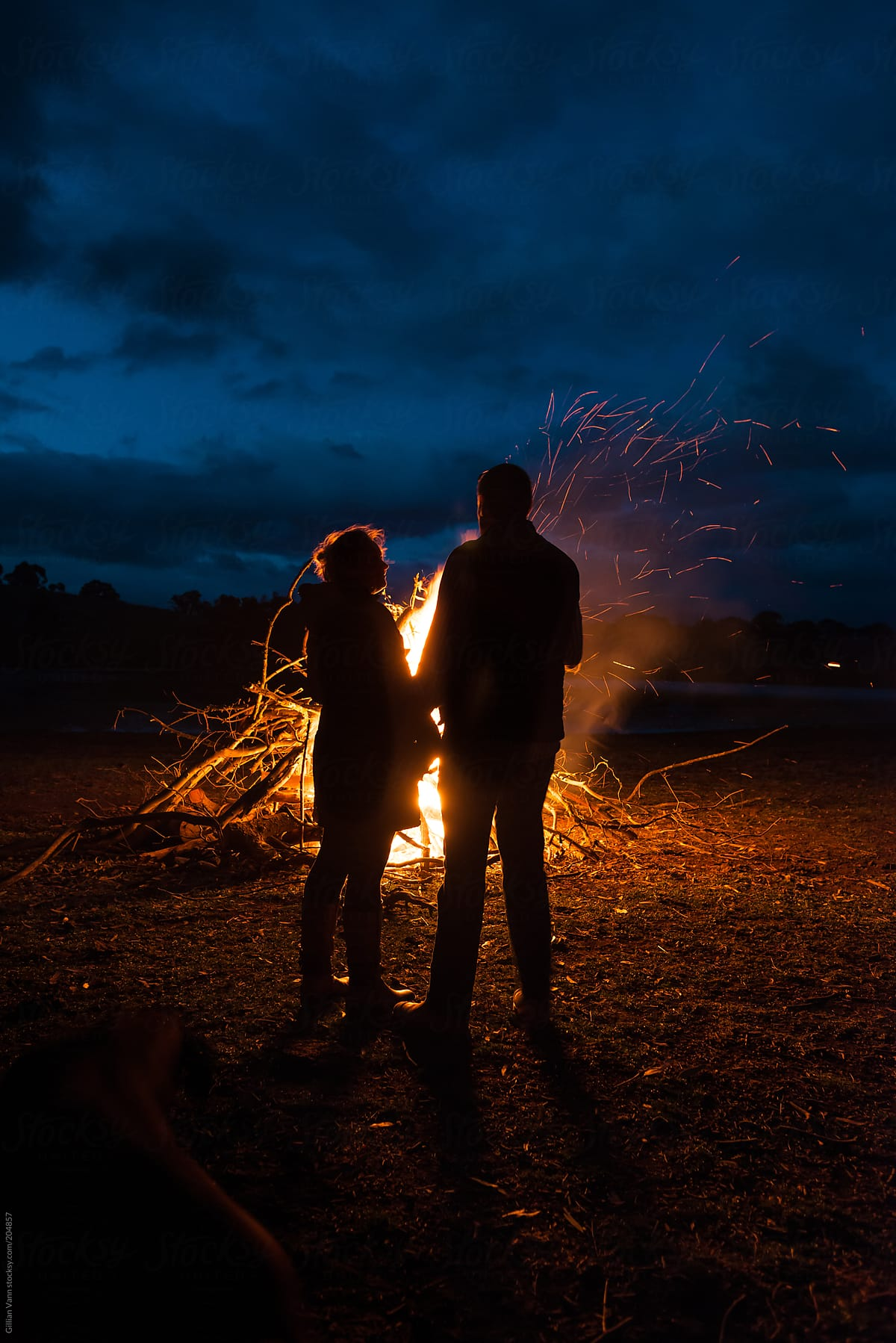 a couple silhouette by the campfire stocksy united