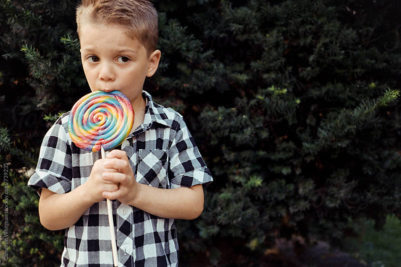 Young boy enjoying a lollipop by Cameron Whitman for Stocksy United