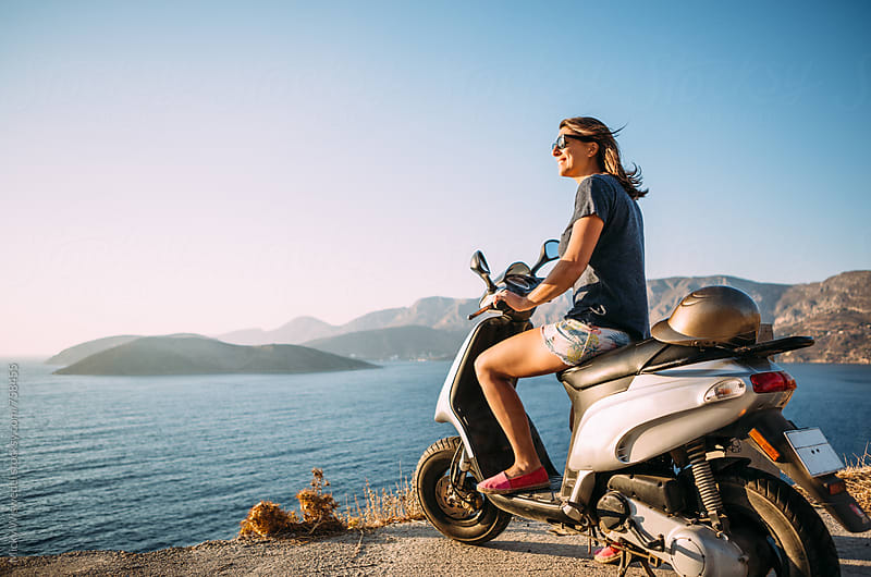 woman on a moped overlooking the sea at sunset by Micky Wiswedel for Stocksy United