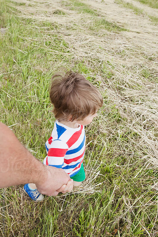 Boy (2 years old) holding his father's hand by Michael Zwahlen for Stocksy United