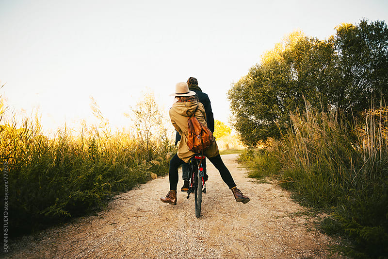 Back view of a hipster couple riding a bicycle in the forest. by BONNINSTUDIO for Stocksy United