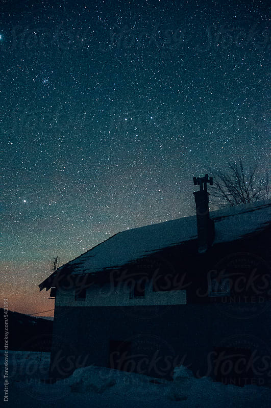 Mountain lodge sillouethe under a starry sky by Dimitrije Tanaskovic for Stocksy United