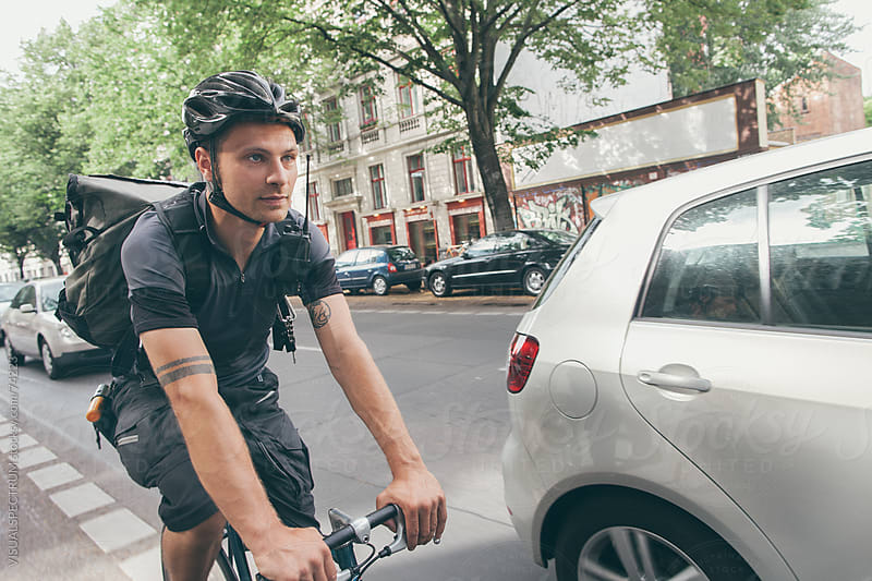 Bicycle Messenger Overtaking Cars by Julien L. Balmer for Stocksy United