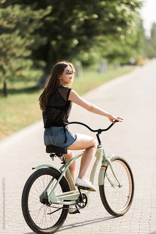 Happy Young Woman Riding a Bike  by Alexey Kuzma for Stocksy United