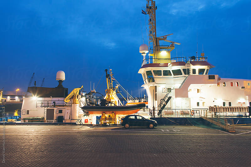 working activity around a ship in the harbour at night by Denni Van Huis for Stocksy United
