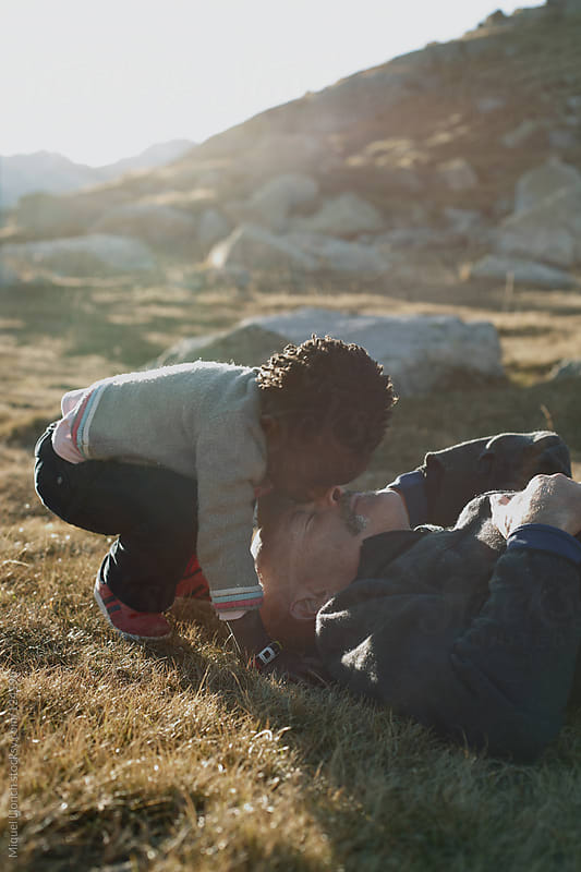 Multiethnic family enjoying nature and love moments by Miquel Llonch for Stocksy United