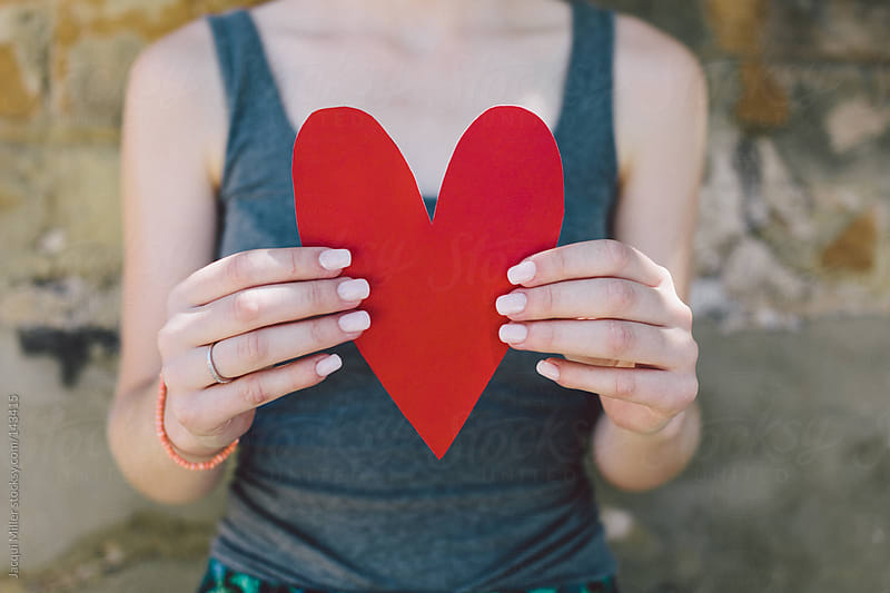 Teenage girl holding a red paper heart in her hands by Jacqui Miller for Stocksy United