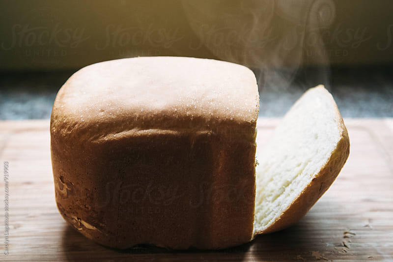 Fresh loaf of white bread with steam coming out of the inside by Carolyn Lagattuta for Stocksy United