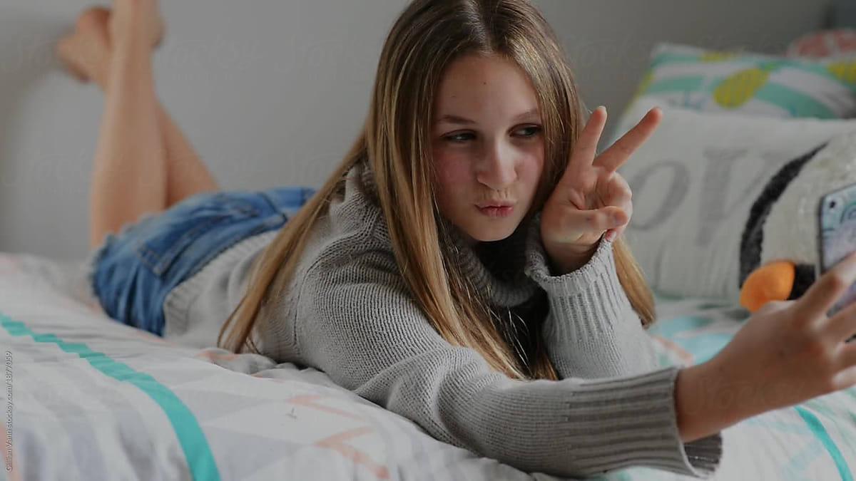 Teen Girl In Bedroom, Taking Selfies On Her Phone By -2563