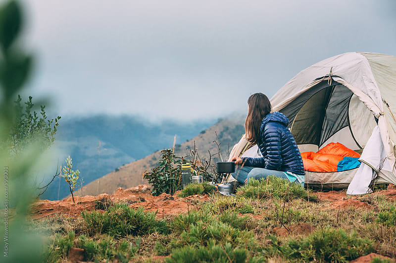 hiker sitting outside her camping tent in the mountains by Micky Wiswedel for Stocksy United
