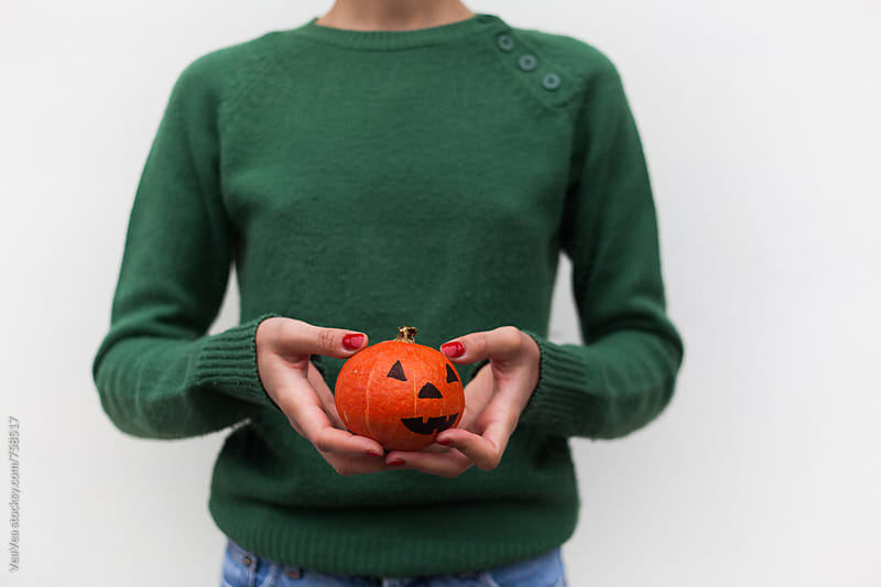 Woman in a green sweater holding a small Halloween pumpkin  by Marija Mandic for Stocksy United