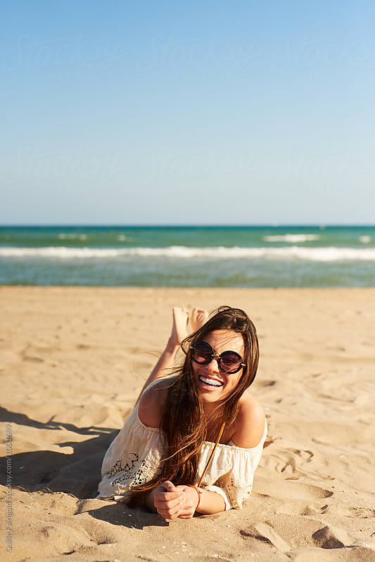 Portrait of girl in sunglasses lying on and by Guille Faingold for Stocksy United