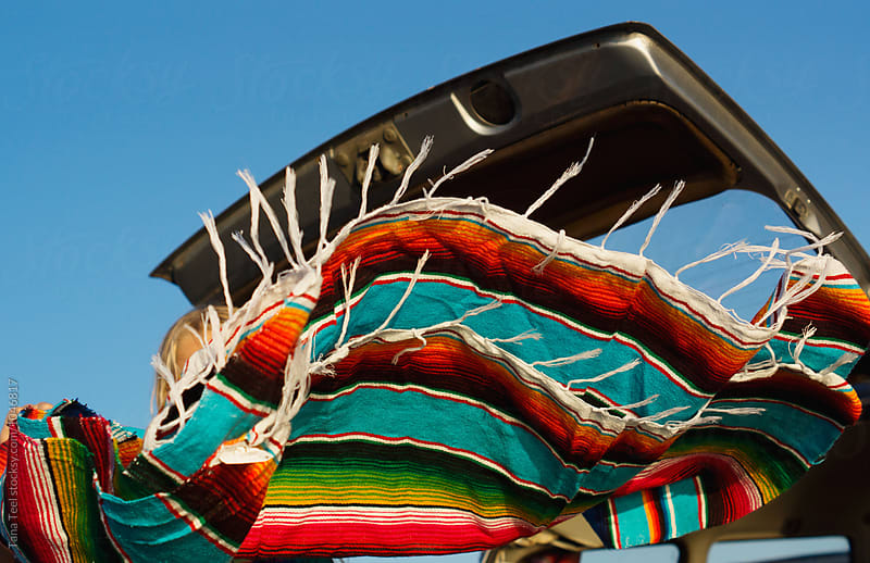 colorful mexican blanket thrown in air by Tana Teel for Stocksy United
