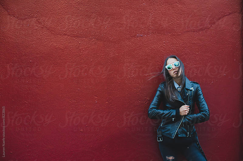 Girl in leather jacket against red wall by Lauren Naefe for Stocksy United