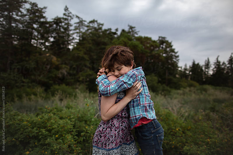 Mom and son spending time together outside in nature - hug by Rob and Julia Campbell for Stocksy United