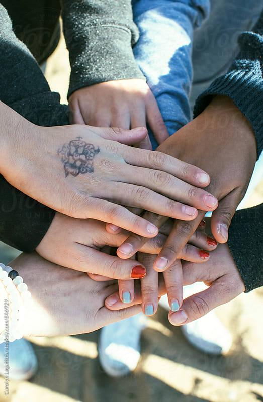 Teenage girls stacked hands by Carolyn Lagattuta for Stocksy United