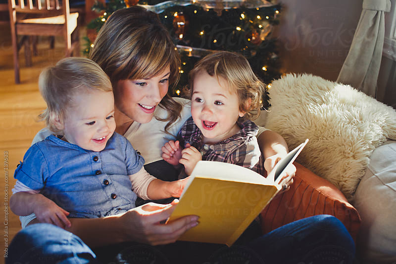 Young mother reading book to kids at christmas  by Rob and Julia Campbell for Stocksy United