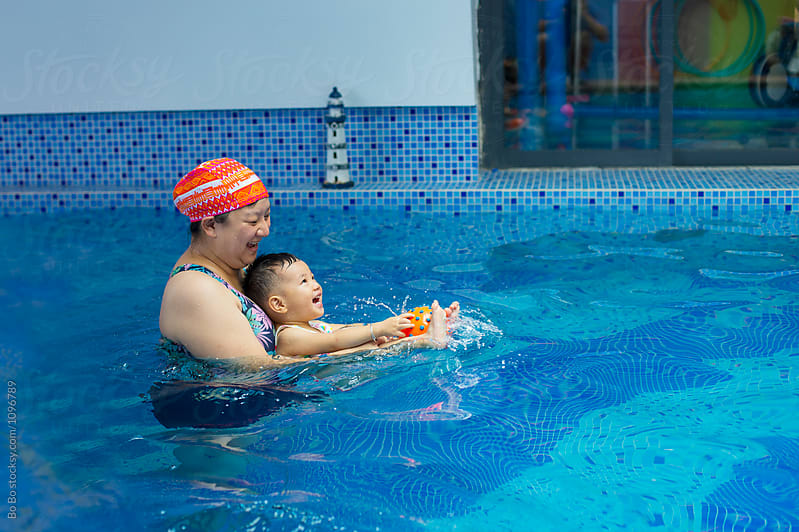 happy woman with her baby girl in swimming pool by cuiyan Liu for Stocksy United