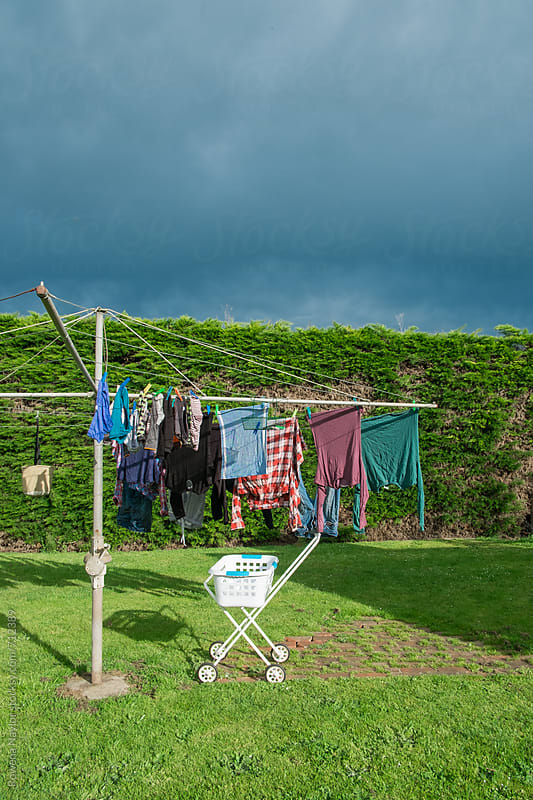 Washing on the line just as rainclouds approach by Rowena Naylor for Stocksy United