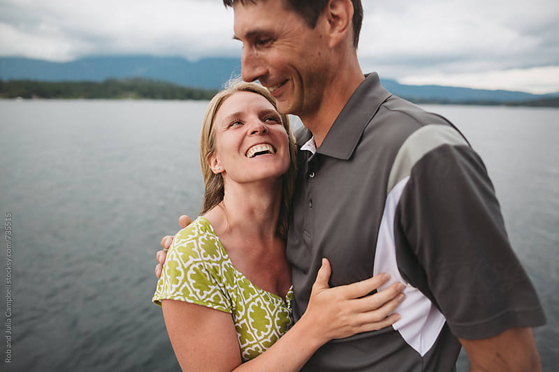 Happy couple in their 40's laughing on the dock at the lake by Rob and Julia Campbell for Stocksy United