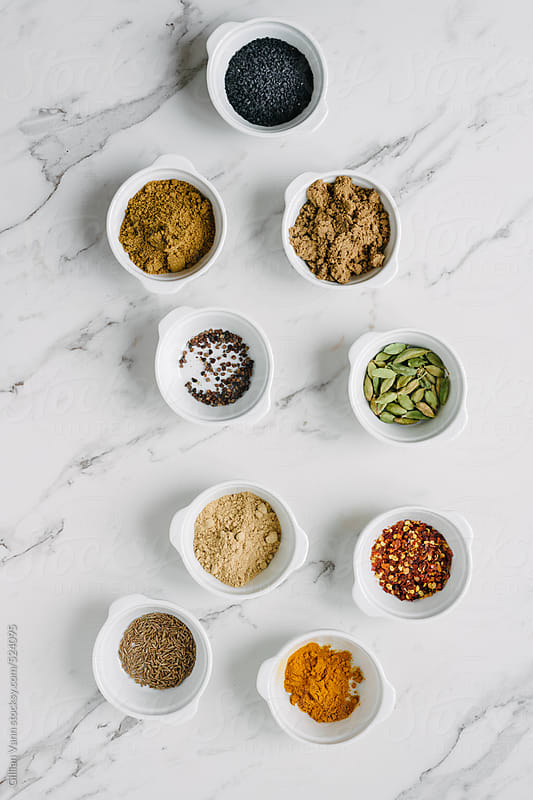 overhead of various spices and seeds in white bowls on a clean marble background by Gillian Vann for Stocksy United