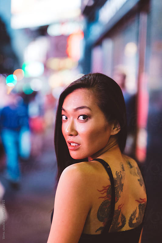 Asian woman with a tattoo on the back by Good Vibrations Images for Stocksy United
