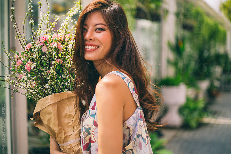 Beautiful Woman Holding Bouquet on the Street by Marija Savic for Stocksy United
