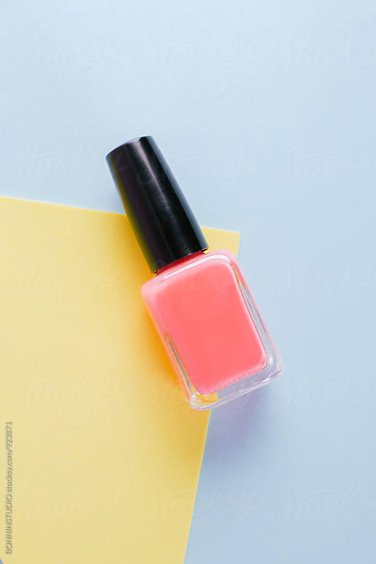 Pink nail polish bottle on colored background. by BONNINSTUDIO for Stocksy United