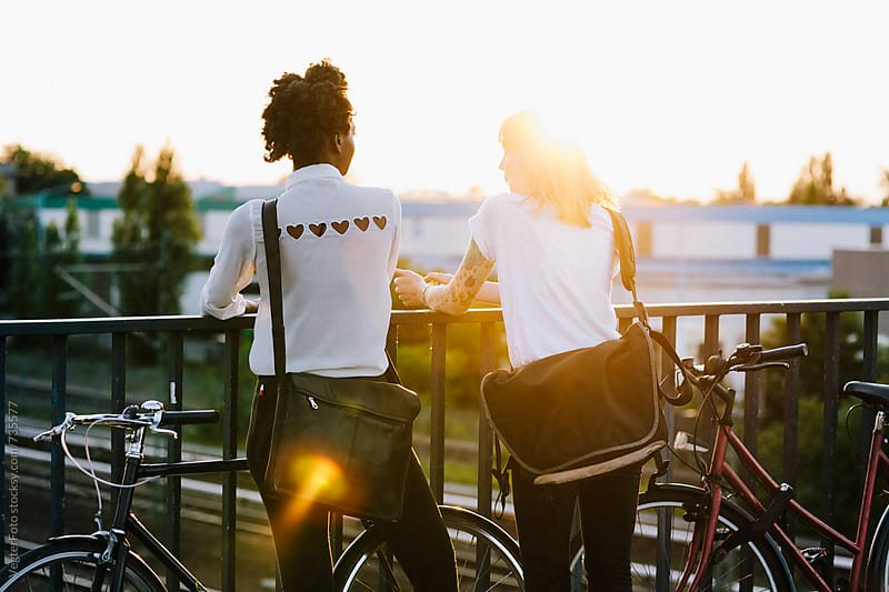 Two women at Sunset with Bicycles by VegterFoto for Stocksy United