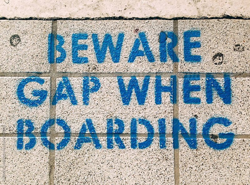 Beware gap when boarding, signal in train subway station by Leandro Crespi for Stocksy United