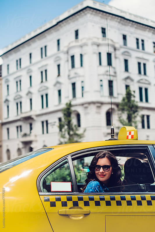 Woman Sitting in a Yellow Taxi by Lumina for Stocksy United