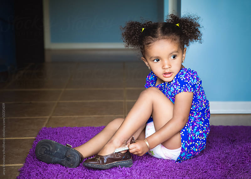 Young cute female with curly pigtails sitting on a purple rug while trying to buckle her shoes by anya brewley schultheiss for Stocksy United