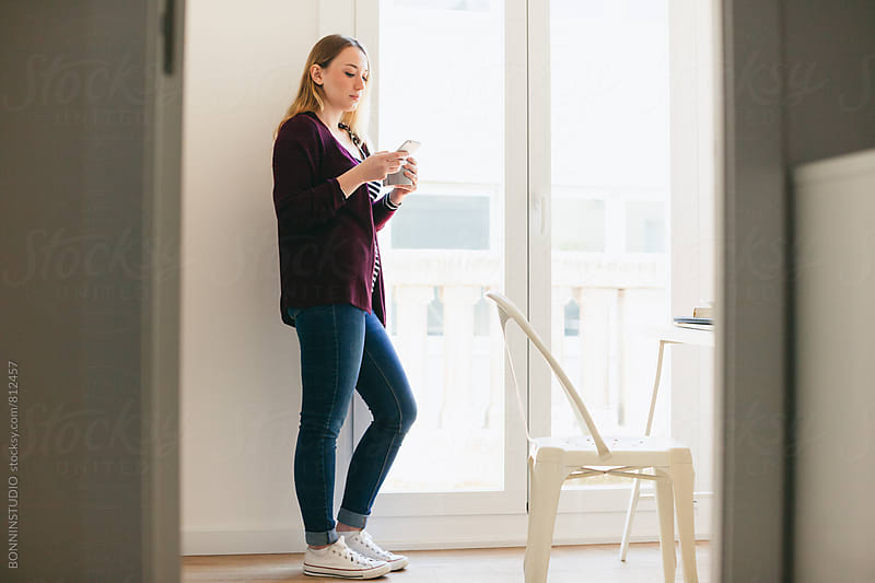 Casual woman using her smartphone standing at home. by BONNINSTUDIO for Stocksy United