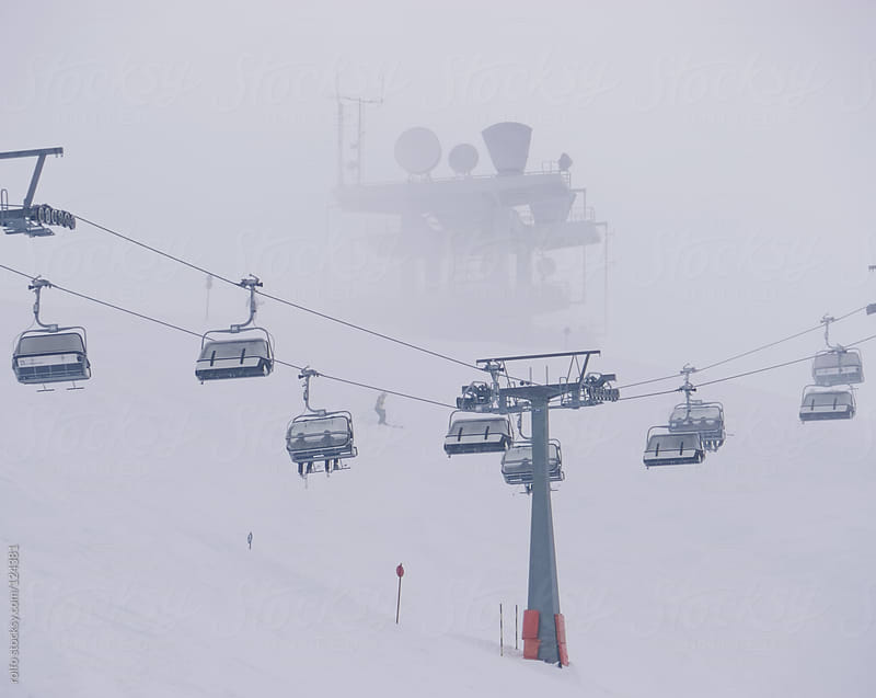 Chairs on a ski lift taking skiers to the piste by rolfo for Stocksy United