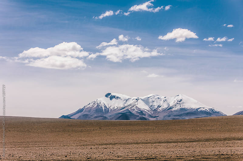 Mountain with snow on the horizon in desert landscape of Andes, South America by Alejandro Moreno de Carlos for Stocksy United