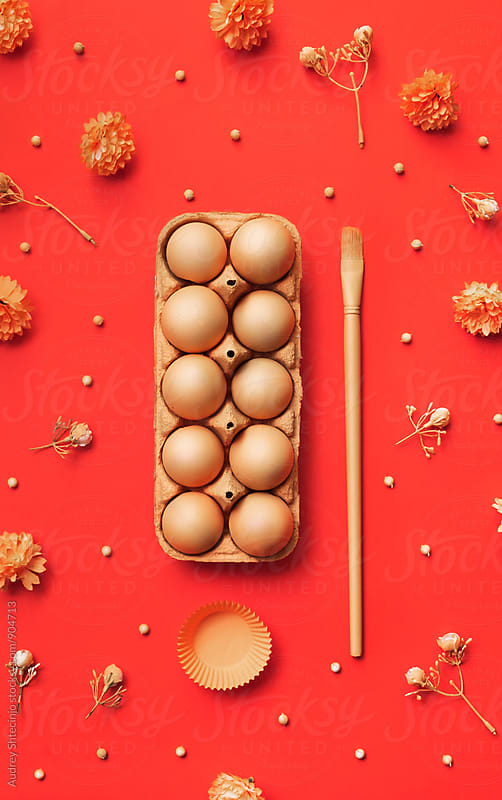 Easter eggs on orange /red background by Marko Milanovic for Stocksy United