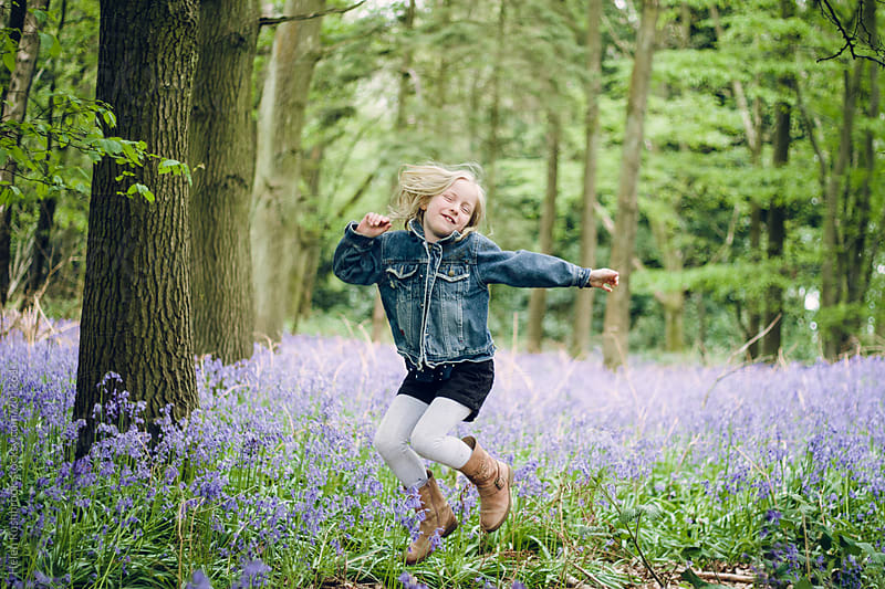 A little girl jumping happily in a bluebell wood by Helen Rushbrook for Stocksy United